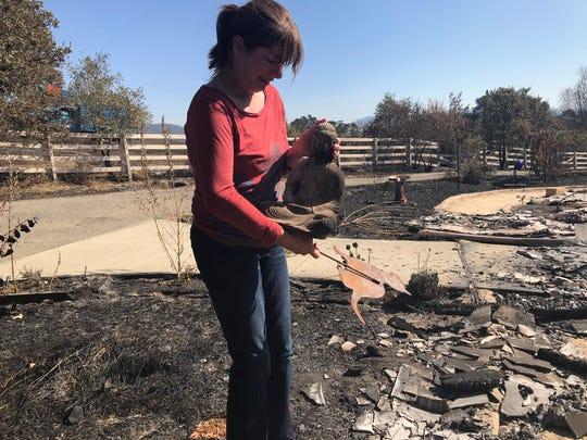 Cassie Taaning-Trotter cradles a Buddha statue that was a gift from a friend after she graduated from college. Taaning-Trotter found it Friday where her home burned down earlier in the week near Redwood Valley in Mendocino County.