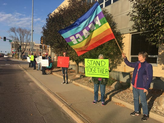 A group of about 20 stands in downtown Sioux Falls