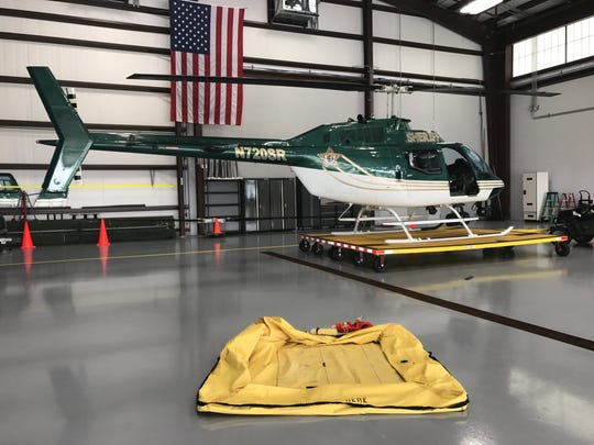 Indian River County Sheriff's Office deputies display the helicopter and raft that helped save the lives of three men after their boat capsized Thursday evenings in waters near the Sebastian Inlet.