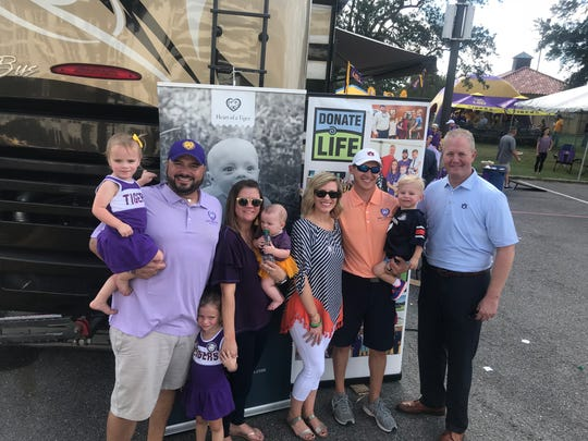 The Perrys and Boswells appear at a Donate Life event with Jay Jacobs, Auburn athletic director, before the LSU and Auburn game on Saturday, October 14, 2017. The face of John Clarke Perry appears on a poster in the background.