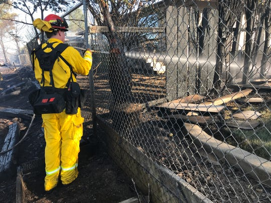 A firefighter sprays water on a burned fence Saturday afternoon behind Woodcliff Drive in Redding.