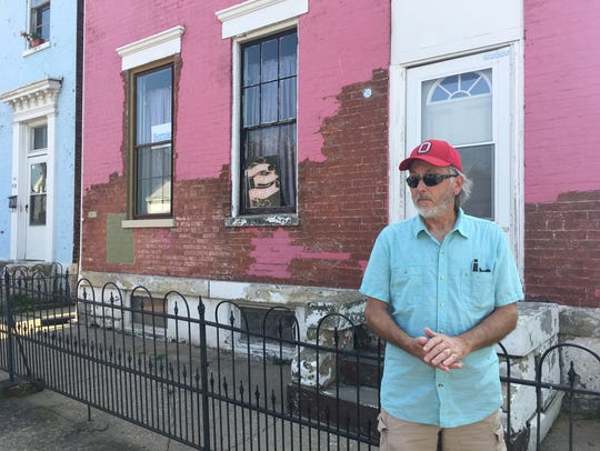 Micky McElwain stands outside his home in Newport's west end. McElwain is rehabbing the home and working to get the neighborhood national historic district status.