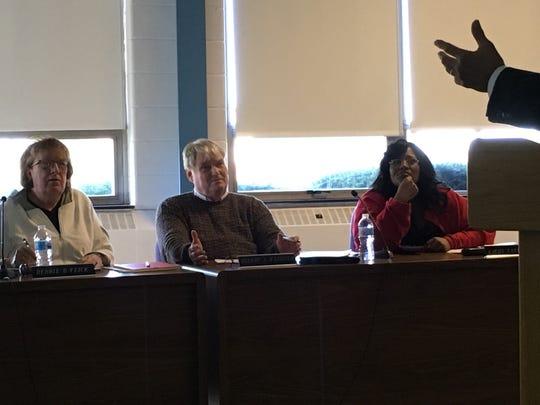 Muncie school board members Debbie Feick, Andy Warrner and Kat Carey listen to chief financial officer Bob Coddington.