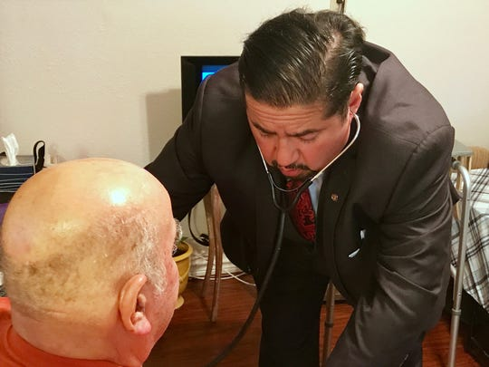 Joe Flores, a licensed nurse practitioner, examines one of his patients during a house call Thursday, Oct. 19, 2017, in Corpus Christi. Flores also practices law.