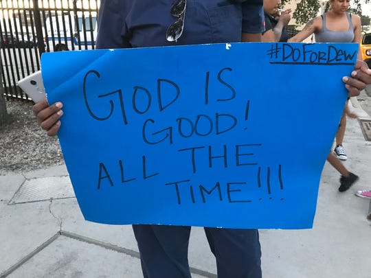 Chantal Guy, 29, holds a poster board with her father Dewboy Lister's favorite quote during a peaceful protest outside the Corpus Christi Police Department on Friday, Oct. 20, 2017.