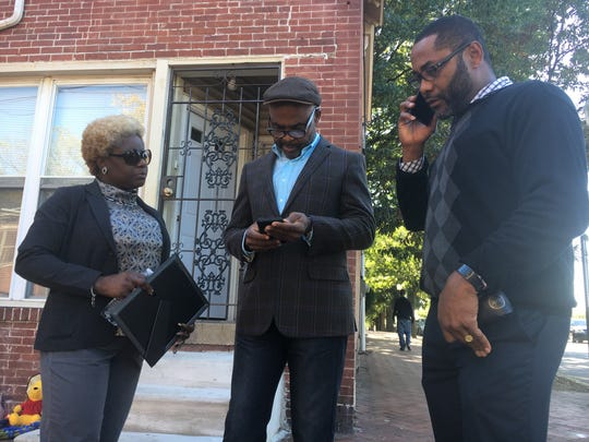 Ajawavi Ajavon (left), of the Delaware African Caribbean Coalition, stands with Sei Boayue and Ernest Kpan, both of the Delaware Liberian Association, outside the Wilmington home shared by Victor Epelle and Kula Pelima. The coalition and the association are searching for ways to help Epelle.