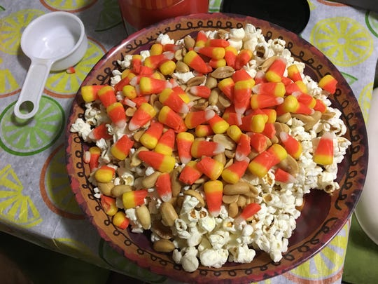 Popcorn pumpkins start off with a big bowl of popcorn, candy corn and salted peanuts. Tip: Use a deep bowl because you will be adding a melted marshmallow mixture later.