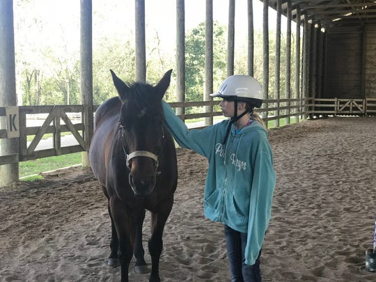 Marlee McNutt, 12, interacts with one of the horses in the arena at Camp Sycamore Hills.