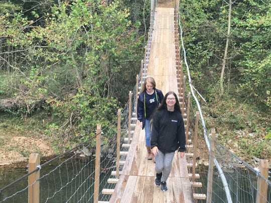 Two girl scouts walk across a bridge as they head toward the equestrian facility after zip-lining at Camp Sycamore Hills.