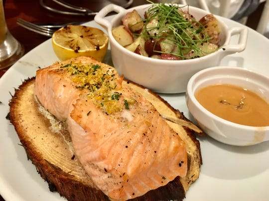 A cedar plank coal-fired salmon ($26) includes a warm, grilled potato and kalamata salad and smoked tomato butter.