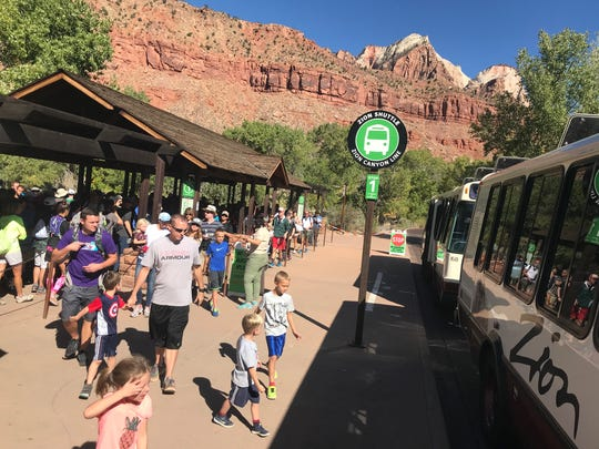 Visitors line up to board shuttle buses at Zion National