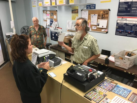Steve Shafer helps customer Hannah Wimmers as senior retail window clerk Max Damron looks on at the post office at The Atrium in south Fort Myers.