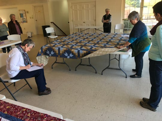 Karen Kendo, right, examines a quilt as she judges entries for the Upcountry Quilting Guild show.