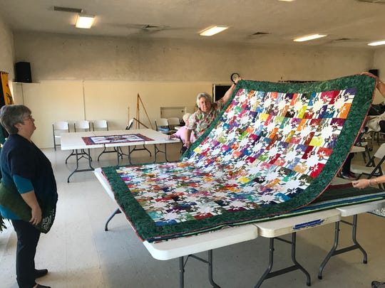 Karen Kendo examines a quilt as she judges entries for the Upcountry Quilting Guild show.