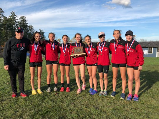 The CVU girls cross-country team poses with the championship trophy at Thetford Academy on Saturday.