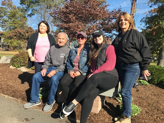 The family of the late Ralph Politi Jr. sits in a garden