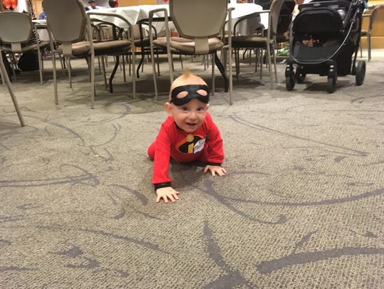 A baby dressed as Jack-Jack from the Incredibles for