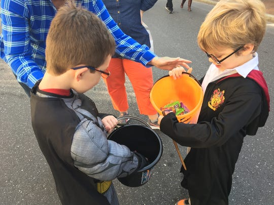 Staunton residents Oliver Torrens, 6, dressed as Batman, and Jacob Miller, 5, dressed as Harry Potter, compare candy during the Halloween downtown trick-or-treating event in Staunton, Va., on Saturday, Oct. 28, 2017.