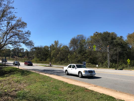 Bicyclists cross W. Blue Ridge Drive while riding on