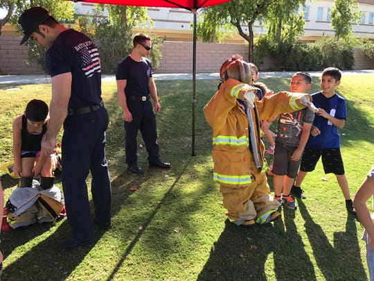 Desert Sands students try on firefighter gear as a