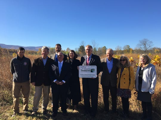 Gov. Terry McAuliffe poses for a photo alongside state natural resource employees and attendees of his announcement of the first project using funds from the South River DuPont Settlement at Cowbane Prairie Natural Area Preserve in Stuarts Draft, Va., on Tuesday, Oct. 31, 2017.