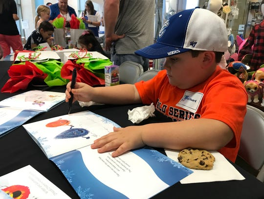Michael Kanatzar, 6, signs his name on a page of the