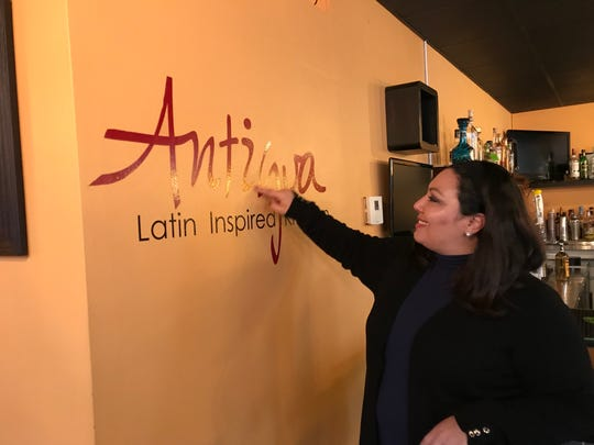 Anitigua restaurant owner Citlali Mendieta built her menu on fresh food and Latin inspired dishes with a unique spin. She is seen here tracing the sign on the wall just as she did when creating the logo. The restaurant is located at 5823 W. Burnham St. in West Allis, WI.