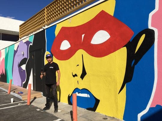 Los Angeles based artist John Moody stands in front of his Batman and Robin themed mural at Trio in Palm Springs. (Nov. 4, 2017)