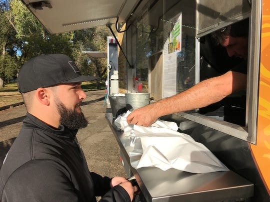 Kyle Dunaway of Eureka pays for an order of pepperoni pizza cones Saturday from The Lamb & The Wolf food truck at Caldwell Park.