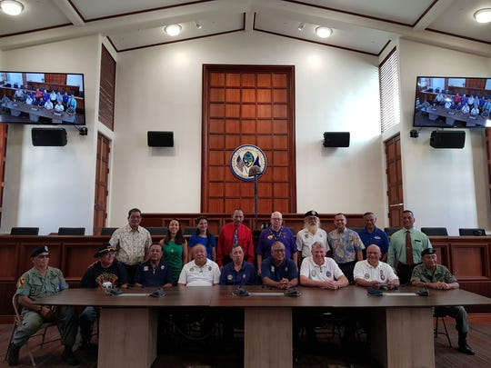 Vietnam veterans take a photo with senators after a flag raising ceremony in honor of them and their fallen brethren at the Guam Congress Building on Nov. 6, 2017.