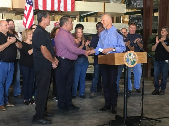 Gov. Rick Scott shakes hands with Hugo Mir, president and CEO of Fort Myers-based Alufab USA, on Monday as co-owner Marco Mesa looks on.