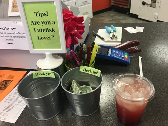 Some lingonberry lemonade next to a tip jar with a question for customers at ScandiHus.