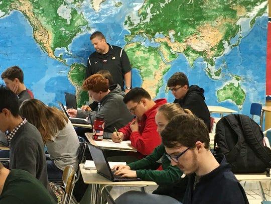 Northwest High School teacher Jeffery Lamb helps Logan