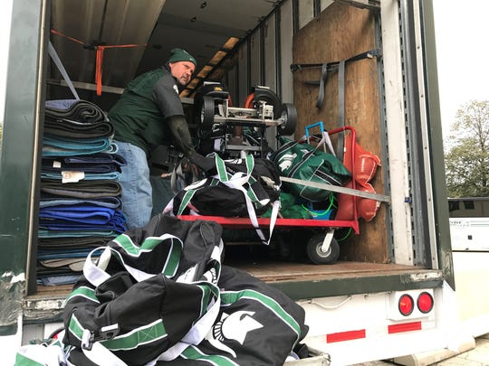 Glenn Edgett tosses Michigan State football player's bags of equipment out of the back of his trailer Oct. 28 outside Ryan Field in Evanston, Illinois more than six hours before the Spartans took on Northwestern.