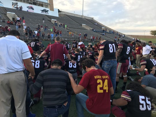 Midwestern State's football team kneels in prayer after