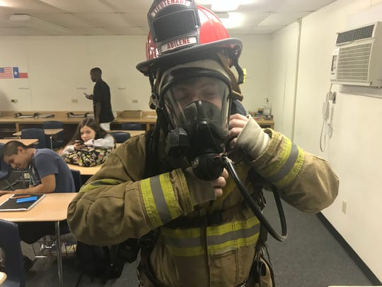 Cameron Mitchell, a sophomore at Abilene High School, wears the protective gear of a firefighter during class where he's learning the basics of being a public servant. Abilene Independent School District officials created a program with the help of the Abilene Fire Department to begin training high school students to be firefighters if they desire.