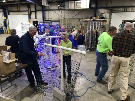 Volunteers work to re-string lights onto Making Spirits