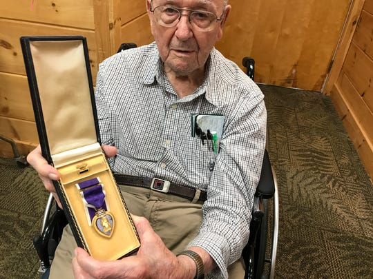 Ormand Williams, 94, displays the Purple Heart he received for combat injuries he sustained in Italy from a German mortar attack.