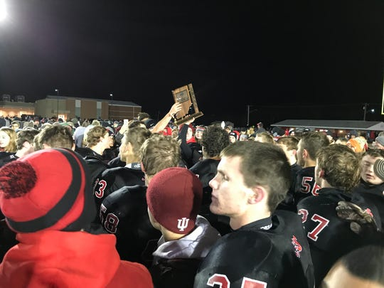 Southridge players hold the Class 2A regional trophy aloft after Friday's 47-7 victory over Providence