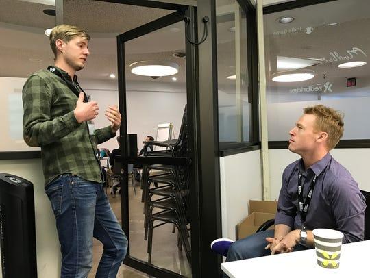 Luke Miner, left, asks a question of facilitator Josh