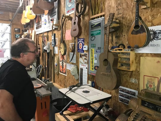 Dan'l Brazinsk looks at one of his handmade instruments.