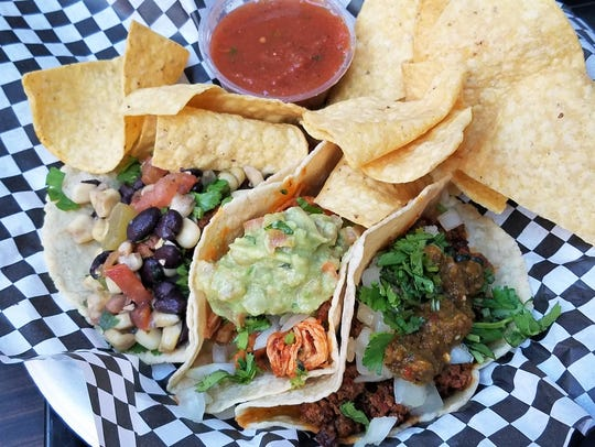 A taco plate with homemade corn tortillas and three