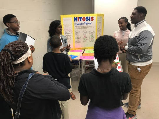 (From left) Peabody Magnet High School Seniors Dana Williams, Kestiny Brevelle and Rocky Countee teach students from Peabody's feeder school, Arthur F. Middle Magnet, about mitosis.