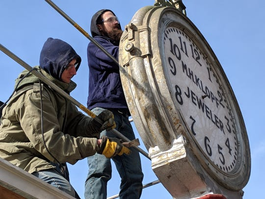 Keith Seib (left) and his son, Zachary, work on repairing the M.H. Klopf street clock outside the Milwaukee County Historical Society.