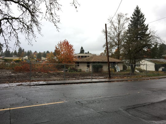 Fencing surrounds two homes on Madrona Ave. SE in Salem, Oregon, on Nov. 16, 2017. The site will be demolished to make way for a Fred Meyer fueling station.