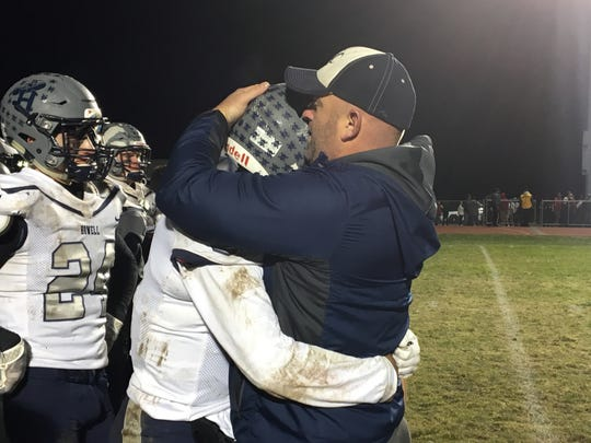 Howell coach Luke Sinkhorn embraces senior quarterback Eddie Morales after the loss to Lenape.