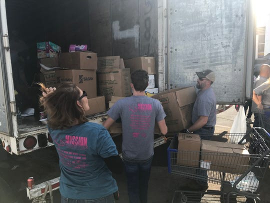 Volunteers pile donations into a truck at Mission Thanksgiving