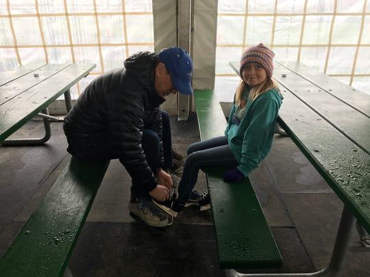 Wally Benson ties his granddaughter's, Caroline, 9,