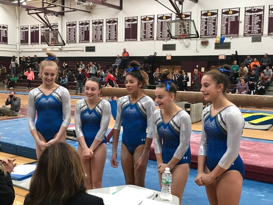 Holy Angels gymnasts (from left) Maggie Kaczmarczyk, Kendall Williams, Ashley Thompson, Faith Furletti and Kathryn Welch present to judges prior to the North 1 sectional beam competition on Nov. 4, 2017.