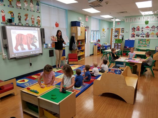 Preschool Teacher, Ms. Cassie, leading a sign language small group activity at The Goddard School.
